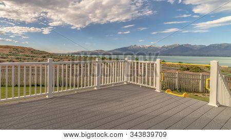Pano Frame Back Porch Of A Home With View Of Lake And Mountain Under Cloudy Blue Sky