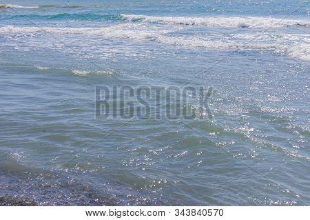 Sea Waves Run A Shore. Foam And Spray Sparkle In The Sun.