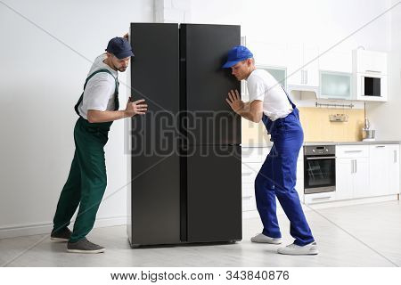 Professional Workers Carrying Modern Refrigerator In Kitchen