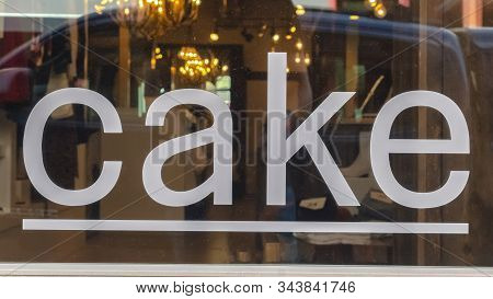 Pano Frame Close Up Of A White Cake Sign On The Shiny Glass Window Of A Store Building