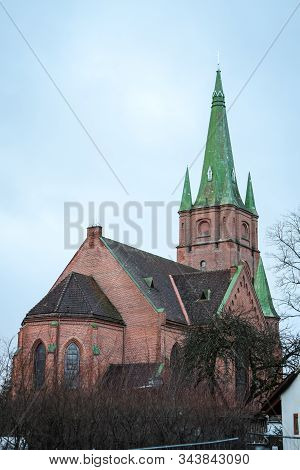 Beautiful View Of Old Red,orange Brick Church With Green Roof With Light Clouds In The Background. P