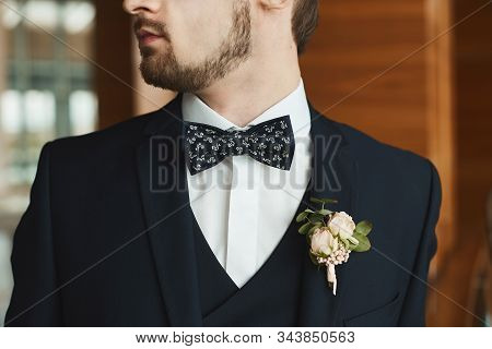 Handsome Stylish Bearded Man In Tuxedo And Bow Tie With A Boutonniere. Young Businessman In A Tailor