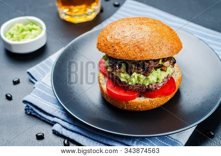 Black Bean Burger With Mashed Avocado, Caramelized Onions And Tomatoes