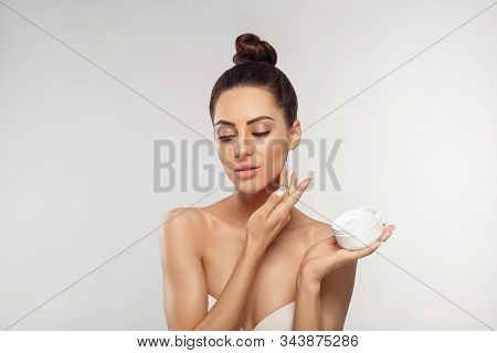 Beauty Concept. Woman Applying  Cosmetics Cream And Smiling. Female Holds A Bottle Cream In Her Hand