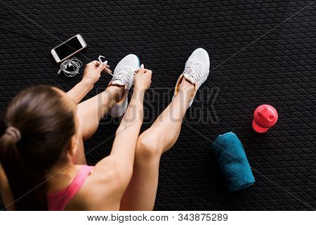 Woman Tying Shoelaces Of White Trainers Siting On A Mat Surrounded By Smart Phone, Earphones, Towel