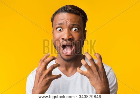 Fear. Frightened Afro Guy Screaming In Fright Holding Hands Near Face Looking At Camera Over Yellow