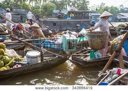MEKONG DELTA, VIETNAM - CIRCA NOVEMBER 2019: Vietnamese farmers sell goods on a daily floating market circa November 2019 in delta of Mekong. Markets in Mekong delta are popular tourists destination.