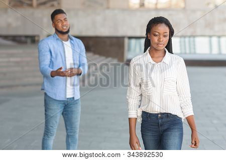 Relationship Crisis And Breakup Concept. Sad Black Man Looking At His Leaving Girlfriend After Their