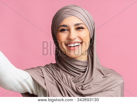 Cheerful Arabic Girl In Hijab Taking Selfie And Sincerely Laughing, Pink Background With Free Space