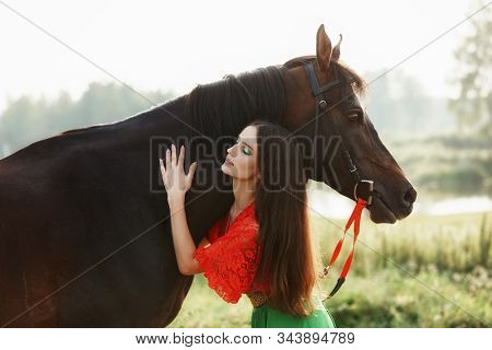 Gypsy Girl Rides A Horse In A Field In The Summer. A Woman With Long Hair Strokes And Caresses A Hor