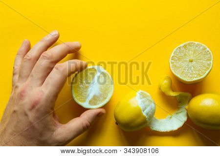 Top View Of Male Hands Holding Whole And Sliced Ripe Lemons On A Yellow Surface, Concept Of Health A
