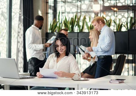 Young Exuberant Female Office Worker Looking At Camera With Lovely Smile At Her Workplace In Meeting