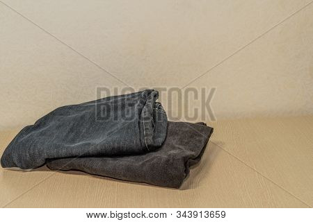 Two Pairs Of Black Denim Jeans Folded Neatly On Wood Grain Table Top.