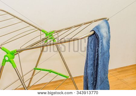 Closeup Of Denim Jeans Hanging Neatly On Fordable Drying Rack.