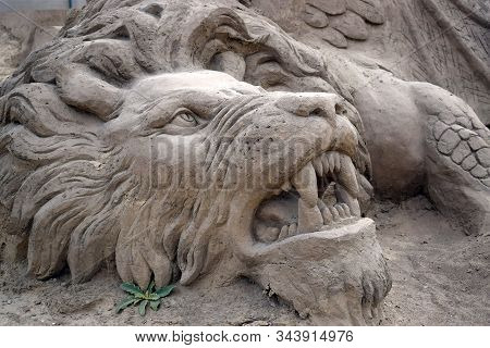 Fragment Of Sculpture From Sand On The Theme Of Mythology. Tearing Lion, Fangs Of Muzzle. Statues Of