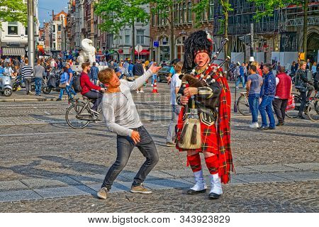Amsterdam, Netherlands - June 11, 2016: A Bagpiper Busking With The Bagpipe On The Dam Square And Ma