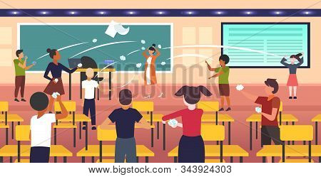 Pupils Demonstrating Bad Behavior Throwing Papers Mocking And Teasing Female Teacher During Lesson B