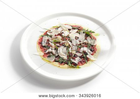 Beef carpaccio with mushrooms, parmesan, fresh arugula and fragrant oil on white restaurant plate isolated. Thin slices of raw veal or venison meat seasoned with vinegar closeup