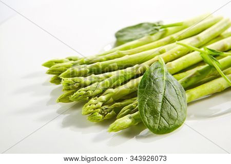 Fresh young asparagus stalks and spinach leaves isolated on white background. Raw garden asparagus or Asparagus officinalis, green vegetable closeup