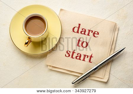dare to start inspirational advice - handwriting on an eco-friendly bamboo napkin with a cup of coffee, business, career, education and personal development concept