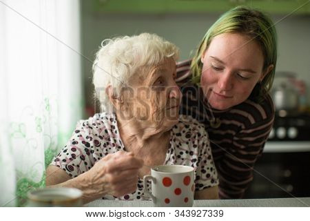 Old woman with her granddaughter at the table in the kitchen at home.