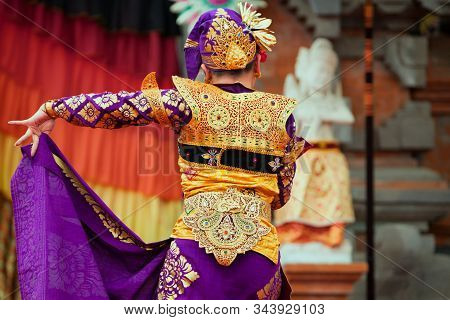 Asian travel background. Group of beautiful Balinese dancer women in traditional Sarong costumes with fans in hands dancing Legong dance. Arts, culture of Indonesian people, Bali island festivals. poster