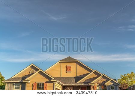 House Exterior With View Of The Gable Roof With Gable Windows Against Blue Sky