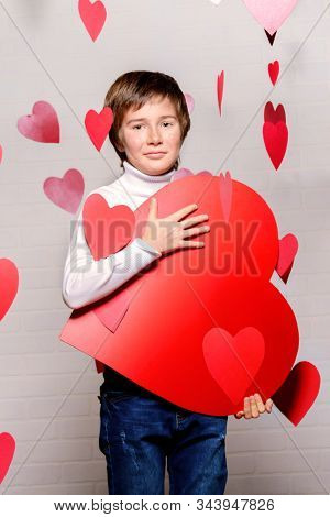 ?ute child boy holding big heart surrounded by little hearts. First love. Valentine's Day.