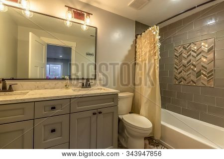 Bathroom With Vanity And Toilet Against White Wall And Bathtub Against Tile Wall