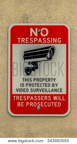 Vertical Building Exterior With Close Up View Of No Trespassing Sign On Concrete Wall