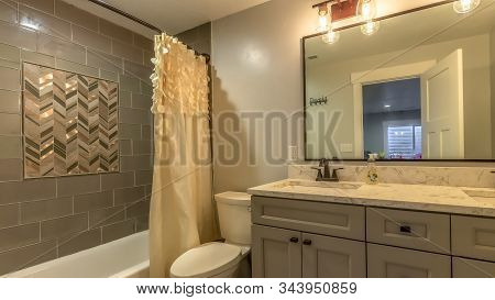 Panorama Frame Bathroom With Vanity And Toilet Against White Wall And Bathtub Against Tile Wall