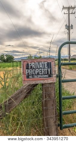 Vertical Frame No Trespassing Sign On The Wire Fence And Green Metal Gate Of Private Property