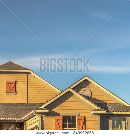 Square Frame House Exterior With View Of The Gable Roof With Gable Windows Against Blue Sky