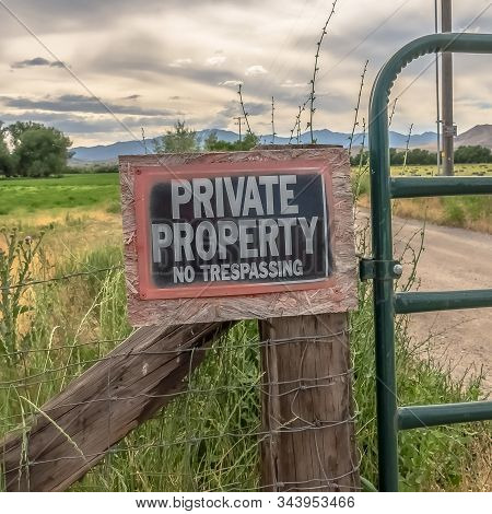 Square Frame No Trespassing Sign On The Wire Fence And Green Metal Gate Of Private Property