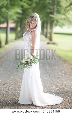 Full Length Portrait Of Beautiful Sensual Young Blond Bride In Long White Wedding Dress And Veil, Ho