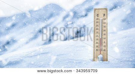 Thermometer On The Mountains In The Snow Shows Temperatures Below Zero. Low Temperatures In Degrees
