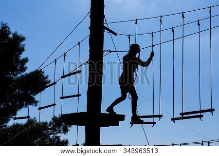Silhouette Of Young Girl In Helmet Climbing On High Rope Course Against Blue Sky. Part Of Obstacle C