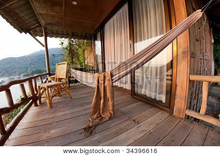 Hammock And Chair On Terrace Of Bungalow
