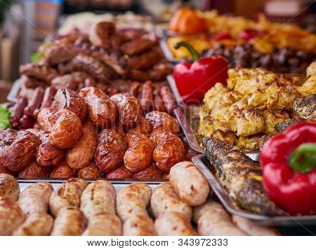 Grilled Meat Variety At Street Food Store, Pork, Beef, Chicken Sausages Stacks And Red Peppers On Tr