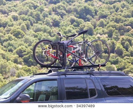 Three Bicycles On The Top Of Car Near Forest