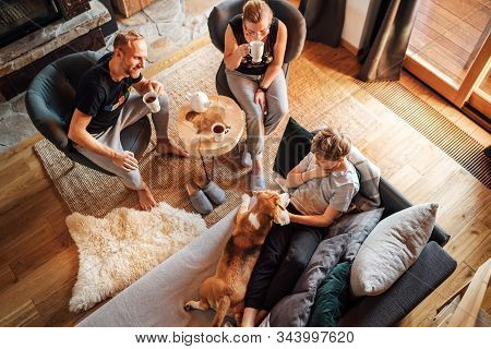 Cozy Family Tea Time. Father, Mother And Son  At The Home Living Room. Boy Lying In Comfortable Sofa