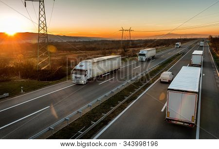 Convoys Of White Transportation Trucks Passing Each Other  On A Highway. Highway Transportation With