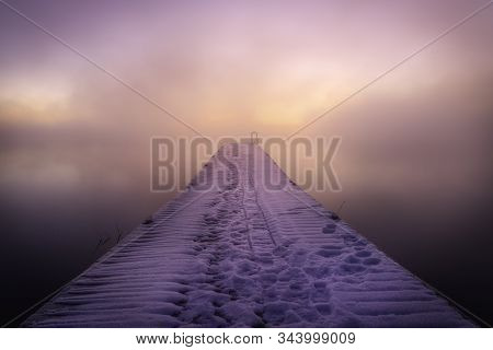Foggy Sunrise On The Fishing Dock After A Snow