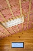Fibreglass insulation installed in the sloping ceiling of a timber house. poster