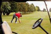 Mature Male Golfer Preparing To Hit Tee Shot Along Fairway With Driver Viewed Through Buggy Window poster