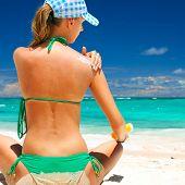 Tan woman applying sun protection lotion poster
