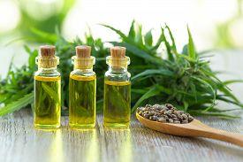Hemp Seeds And Hemp Oil On Wooden Table. Hemp Seeds In Wooden Spoon And Hemp Essential Oil In Small