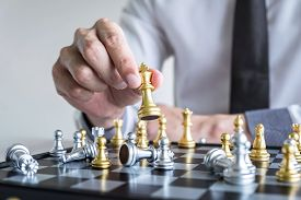 Gold And Silver Chess With Player, Hands Of Businessman Moving Chess Figure In Competition To Planni