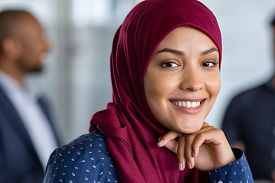Portrait of young muslim woman wearing hijab in office while looking at camera. Close up face of arabic business woman covered with headscarf smiling. Successful arab businesswoman in modern office.