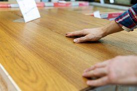Man Touching Wood Texture Of Laminate Floor Sample In Flooring Shop